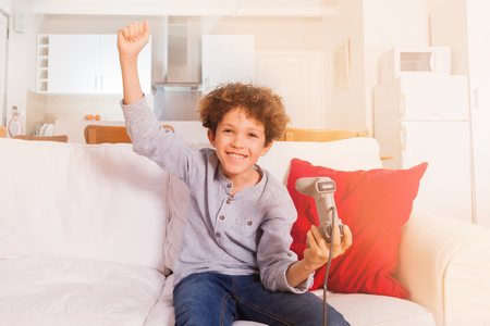 Happy boy holding game controller of videogame
