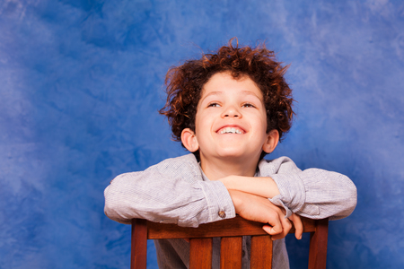 Boy looks upward while sitting backwards on chair Stock Photo