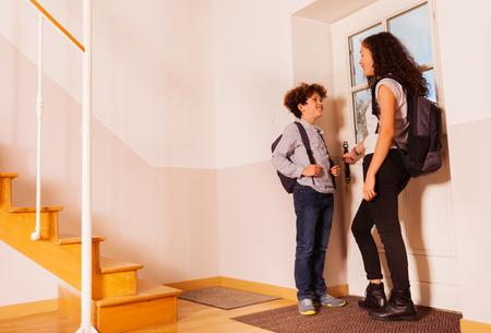 Happy children opening the door leaving to school Stock Photo
