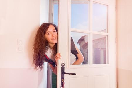 Cute teenage girl looking through front door Stock Photo