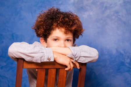 Boy with curly hair sits backwards on wooden chair Stock Photo