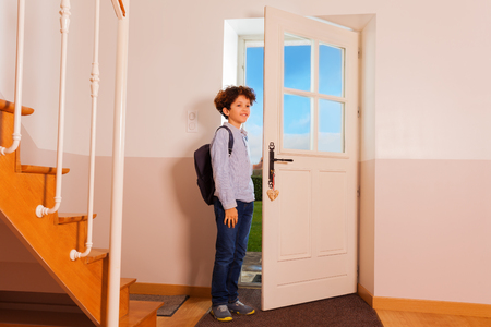 Preteen boy coming back home from school Stock Photo