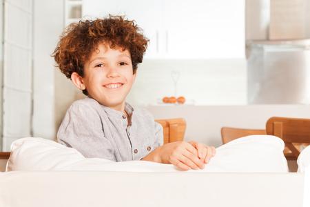 Curly-haired boy sitting backwards on white sofa Stock Photo