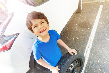 Happy boy standing next to the car with spare tire Stok Fotoğraf
