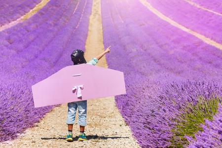 Boy wearing pilot costume plays in lavender field