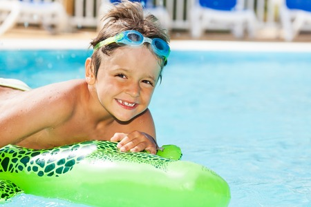 Boy in goggles swimming with inflatable toy