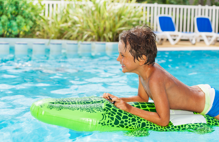 Boy floating on inflatable toy in swimming pool Reklamní fotografie