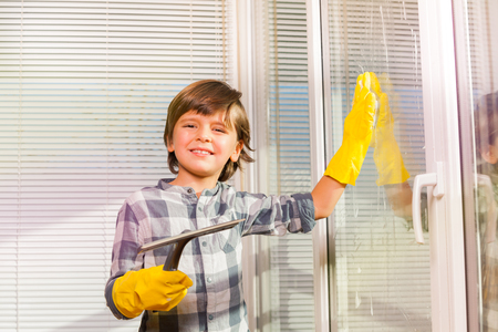 Portrait of seven years old boy in yellow rubber gloves washing windows with sponge and brush