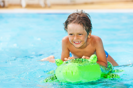 Boy riding inflatable toy in swimming pool