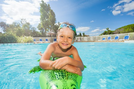 Happy boy relaxing on inflatable toy in pool
