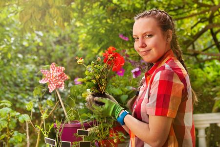 Smiling girl holding geranium plant on terrace