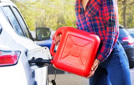 プラスチック製のキャニスター充填車タンクを持つ女性