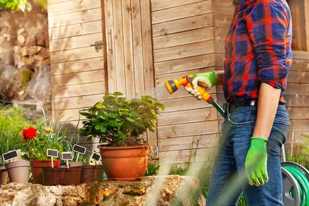 Man watering plants using hand sprinkler outdoors 版權商用圖片