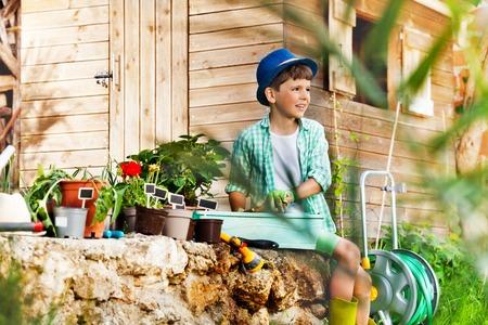 Funny little boy potting plants in the garden