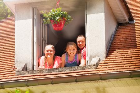 Three smiling girls in the open attic window