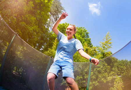 Energetic girl jumping on the trampoline in park Stock Photo