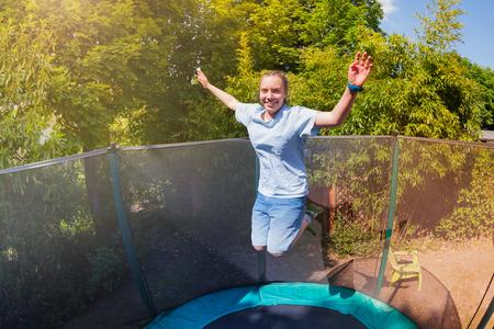 Happy teenage girl playing on trampoline outside