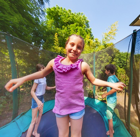 Cute girl jumping on a trampoline with her friends