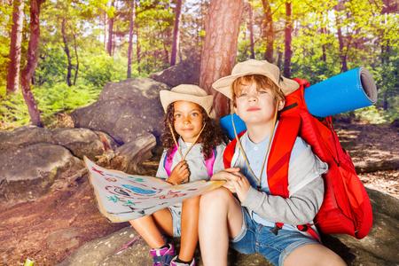Deux enfants en forêt naviguent avec une chasse au trésor sur la carte
