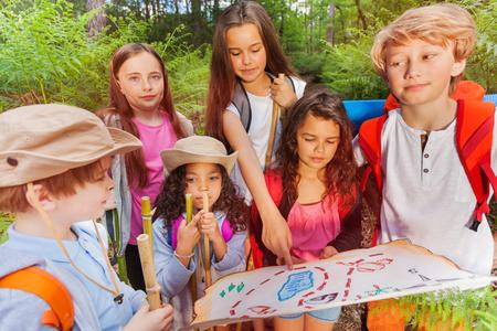 Dzieci z mapą na aktywność nawigacyjną w poszukiwaniu skarbów