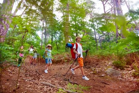 Group of kids on hike trail walk with backpacks