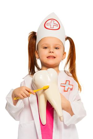Little girl wearing whites brushing tooth model