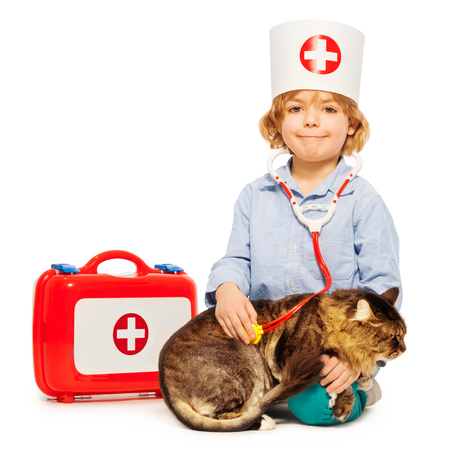 niño jugando veterinario con estetoscopio y gato