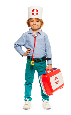 Young boy in doctors cap and with toy instruments