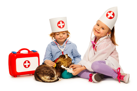 Children dressed at whites bandage paw to a cat Stock Photo