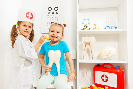 Girl dressed like a dentist examined her friend
