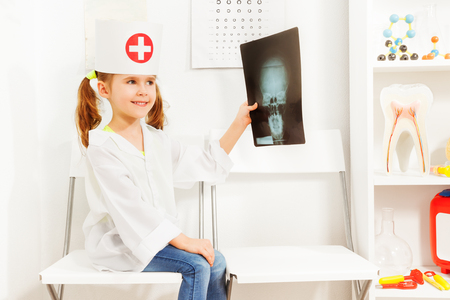 Girl uniformed as doctor with skull radiography