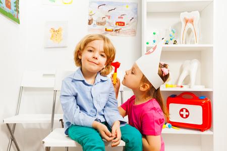 Cute ear nose throat specialist examining boy