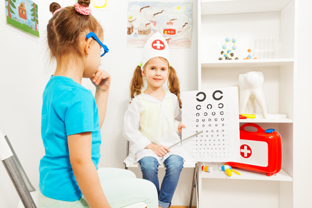 Little girls playing a doctor ophthalmologist Stock Photo