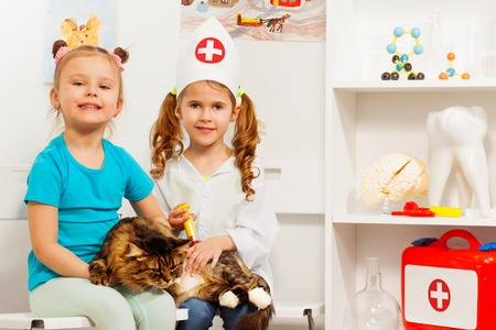 Girls and cat at the veterinary getting a vaccine