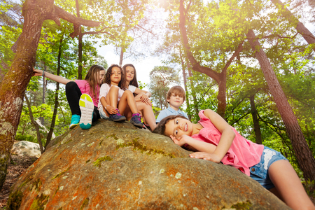 Portrait of large group of kids sitting on the stone together on summer school vacation trip