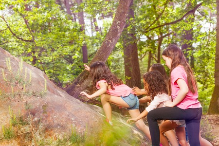 Group of small girls climb on the rock in the forest one after another in casual clothing profile view