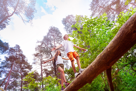 View from bellow of a boy and girl walking over big log high in the air holding balance with hands Imagens