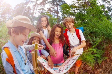 Group of happy children boys and girls with treasure hunt game map discussing route in forest learning navigation in summer camp 版權商用圖片