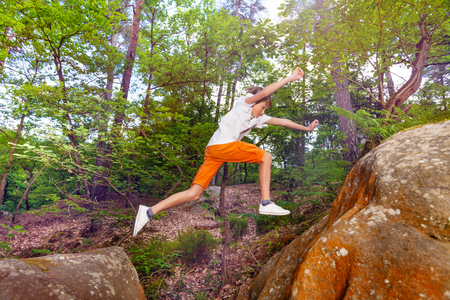 Portrait of a boy long jumping from one rock in the forest to anther Stock Photo