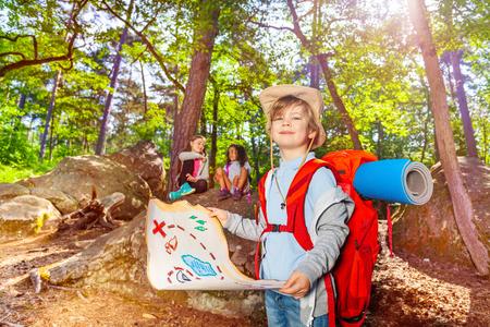 Muchacho del juego del campamento de verano con el mapa del tesoro y otros niños en la orientación del bosque