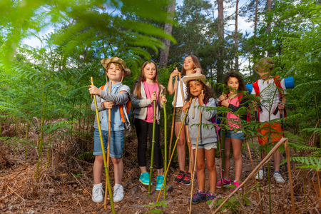 Group of kids stand in the forest resting during hike holding handmade hiking poles sticks mane of bamboo