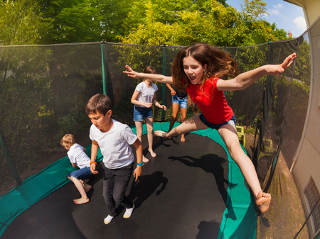 Portrait of happy preteen girl, jumping on the backyard trampoline with her friends during summer vacation 写真素材