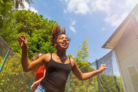 Portrait of happy African girl jumping on the trampoline with her friends outdoors in summer