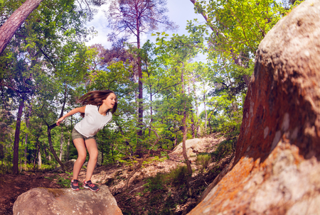 Girl jump high from one rock to another in the forest  with stretched hands and legs