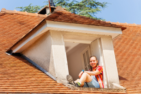 Portrait of happy girl teenager looking down to street from open attic window at sunny day