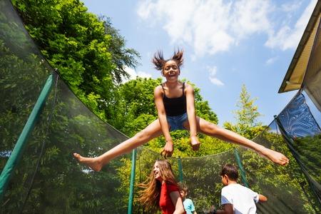 Adolescente africana divirtiéndose saltando en el trampolín del patio trasero junto con sus amigos en verano Foto de archivo