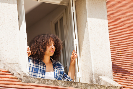 Portrait of beautiful African teenage girl in country house attic window Stock Photo