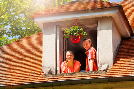 Portrait of two happy friends, Caucasian teenage girls, looking down to street from open attic window Stock Photo