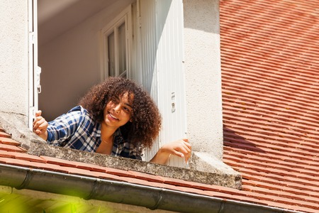 Portrait of beautiful African girl teenager opening shutters and looking out the attic window