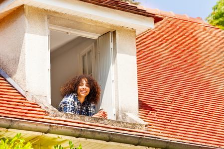 Portrait of African teenage girl enjoying morning in the open attic window